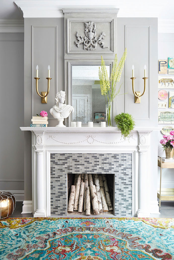 Grey living room design with fireplace mantel, wall panels, brass sconces and cove molding